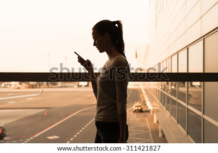 Young female using her phone while walking through the airport.  - stock photo