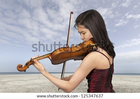 young female violin player outdoors at the beach - stock photo