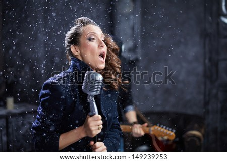 Young female vocalist sings into microphone during shooting video clip - stock photo