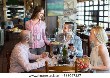 Young female waiter serving restaurant guests. Selective focus - stock photo