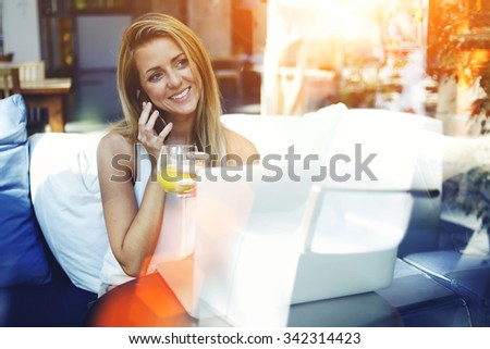 Young female with amazing smile speaking on cell telephone while sitting in front open laptop computer in modern interior, charming woman talking on smart phone while resting after work on net-book  - stock photo