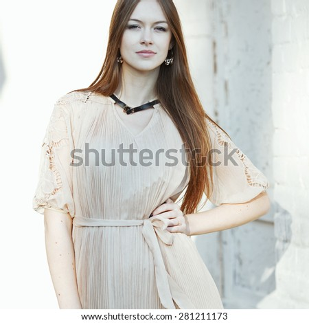 Young female with beautiful long hair posing against brick wall. - stock photo