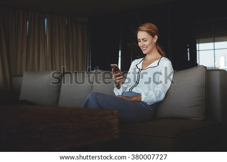 Young female with beautiful smile chatting on mobile phone while sitting in comfortable modern restaurant, businesswoman reading good news on cell phone from her partner while enjoying rest in cafe - stock photo