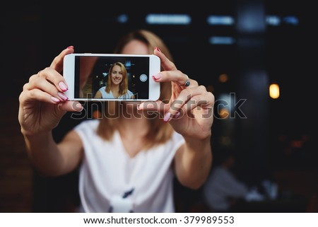 Young female with beautiful smile photographing herself on mobile phone for social network pictures, charming woman making self portrait with cell telephone camera while relaxing in modern coffee shop - stock photo
