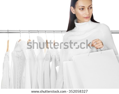 Young female with white shopping bags. Selection of winter clothes on background. Space for text. Sale season concept.   - stock photo