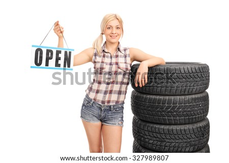 Young female worker holding an open sign and leaning on a set of black tires isolated on white background - stock photo