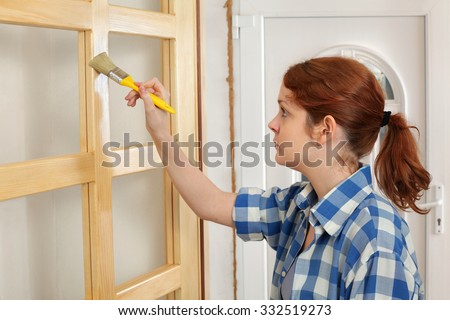 Young female worker painting new wooden door with paintbrush - stock photo