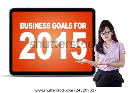 Young female worker with hands gesture showing business goals for 2015 on a board - stock photo