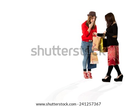 Young females at shopping moll. Two young ladies discuss brand new purchases - stock photo