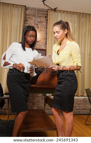 young females at the office talking about a project  - stock photo