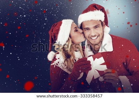 Young festive couple against snow - stock photo