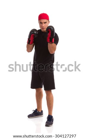 Young Fighter. Confident man in sport shorts, black t-shirt and sneakers posing with boxing gloves. Full length studio shot isolated on white. - stock photo