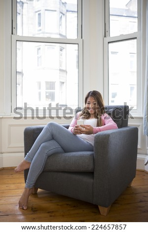 Young Filipino woman at home relaxing in her lounge and using a smartphone - stock photo
