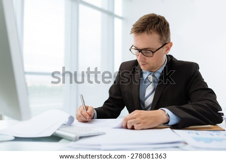 Young financial manager signing business documents - stock photo
