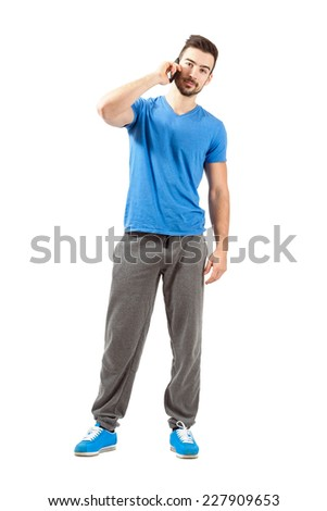 Young fit athlete in sportswear talking on the phone looking at camera. Full body length portrait isolated over white background. - stock photo