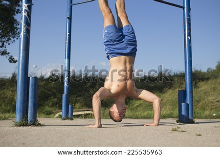 Young fit athlete man doing Handstand Push-Up - stock photo
