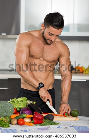 young fit bodybuilder in the kitchen, cooking, cutting vegetables - stock photo