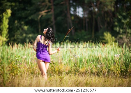 Young fit brunette woman teasing with short dress on forest background in summer - stock photo