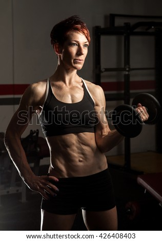 Young fit caucasian female bodybuilder in old school gym - stock photo
