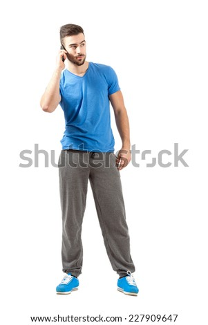 Young fit guy in sportswear talking on the mobile phone looking away. Full body length portrait isolated over white background. - stock photo