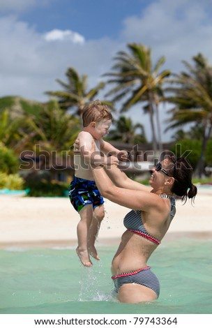 Young fit happy mother playing with her little son in the ocean - stock photo