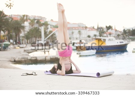 Young fit healthy woman practicing yoga candle pose.Healthy lifestyle and regular exercising routine concept.Yoga and pilates stretching,on beach near dock,seaside.Body and soul harmony and relaxation - stock photo