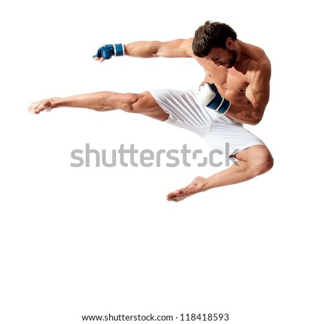 young fit man jumping, high kick and fist punch, muay thai equipment - stock photo