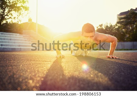 Young fit shirtless Caucasian man doing push-ups outdoors on sunny summer day. Fitness and sport lifestyle concept. - stock photo