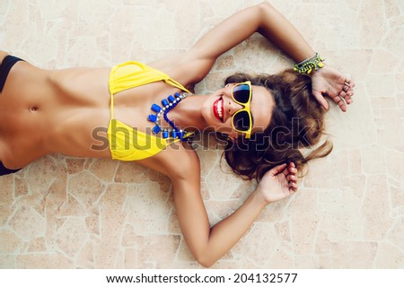 Young fit tan sexy brunette posing outdoor in summer time in stylish yellow bikini and sunglasses, laying and getting sunbathe. - stock photo