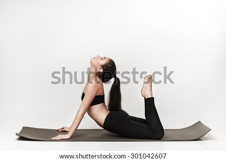 Young fit woman at yoga class. Attractive brunette woman with pony tail practicing yoga. Healthy lifestyle and sports concept. Series of exercise poses. Isolated on white. - stock photo