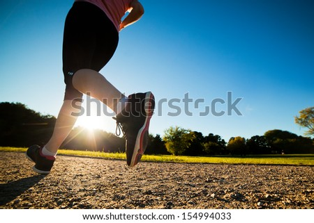 Young fit woman does running, jogging training in a park at summer sunny day. Legs close up - stock photo