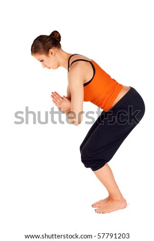 Young fit woman doing first stage of yoga exercise called: Twisted Chair Pose, sanskrit name: Parivrtta Utkanasana, isolated on white background - stock photo