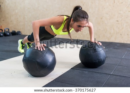 Young fit woman doing push up on medicine ball at gym. - stock photo