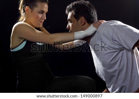 young fit woman fighting a man. battle of the sexes. - stock photo