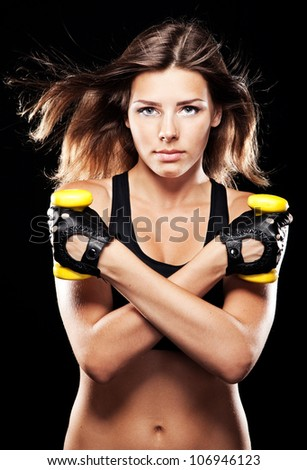Young fit woman in sports outfit, black background - stock photo