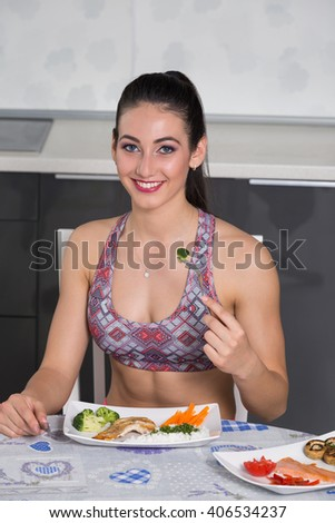 young fit woman in the kitchen, with two plates of healthy food: rice, chicken grill, broccoli, carrots, mushrooms, salmon, tomato, red peppers - stock photo