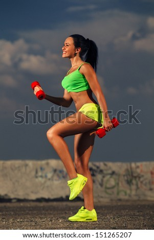 Young fit woman lifting dumbbells against sky - stock photo