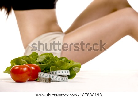 Young fit woman's body with vegetables on white background. - stock photo