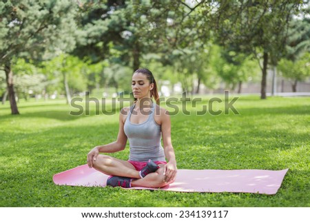 young fit woman sitting on yoga mat and meditating in silence. - stock photo