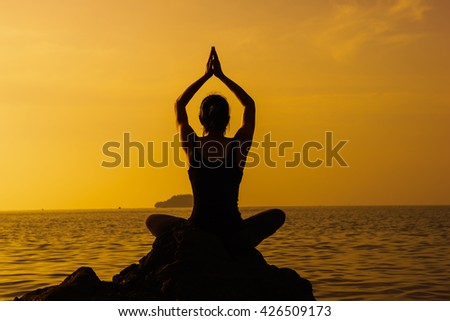 Young fit woman using yoga technique for meditation and well-being on beach at sunrise - stock photo