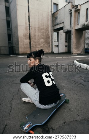 young fit woman with modern haircut sitting on longboard. she is in the shade of building. she wears jeans and sweatshirt. She has tattoos throughout her body. longboard has no prints or aerography - stock photo
