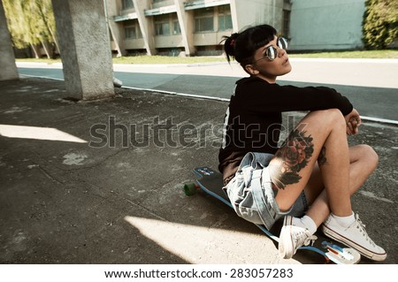 young fit woman with modern haircut sitting on longboard. she is in the shade of building. she wears shorts and sweatshirt. She has tattoos throughout her body. longboard has no prints or aerography - stock photo