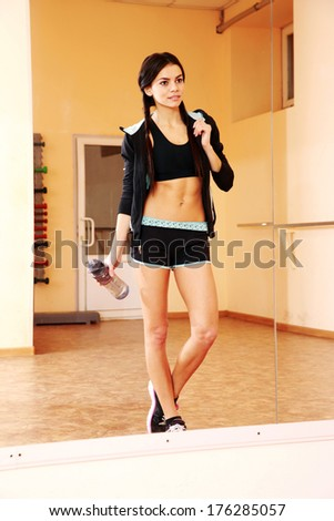 Young fit woman with water looking at her reflection at gym - stock photo