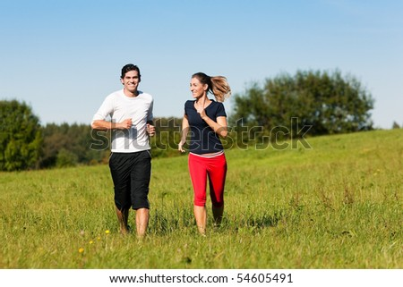 Young fitness couple doing sport outdoors, jogging on a green summer meadow in the grass under a clear blue sky - stock photo