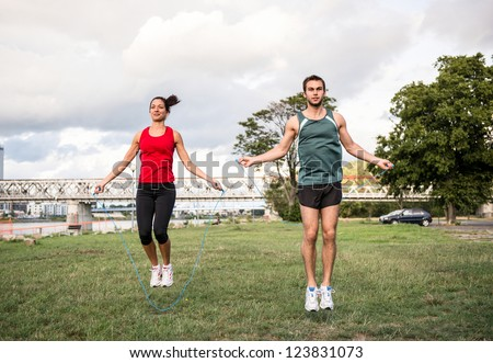 Young fitness couple exercising outdoor - jumping with skipping rope - stock photo
