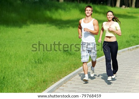 Young fitness couple of man and woman doing jogging sport outdoors - stock photo
