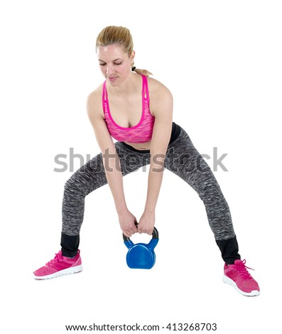 Young fitness female exercise with kettle bell. Mixed race woman doing crossfit workout on grey background. Kettlebell swing. - stock photo