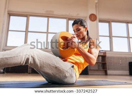 Young fitness female exercising with kettle bell. Muscular young woman in sportswear doing crossfit workout in gym. - stock photo