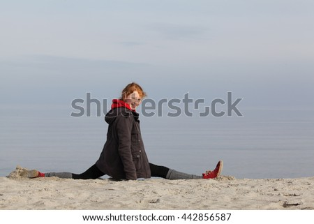 Young fitness girl a the beach in winter - stock photo