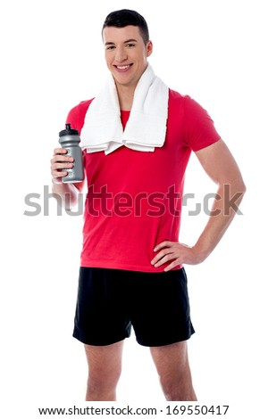 Young fitness man holding sipper, towel around his neck - stock photo